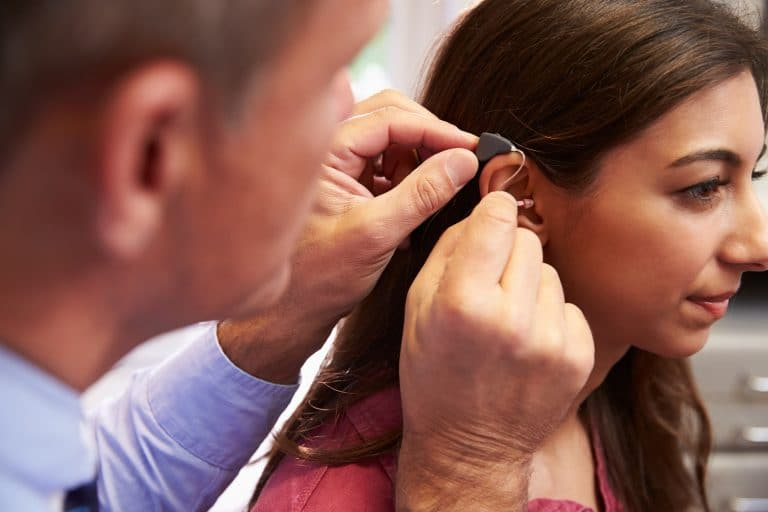 Woman gets hearing aid fitting